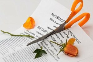 A pair of scissors sliding through a marriage certificate and a flower stem