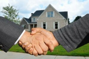 Two men shaking hand and a house in the background